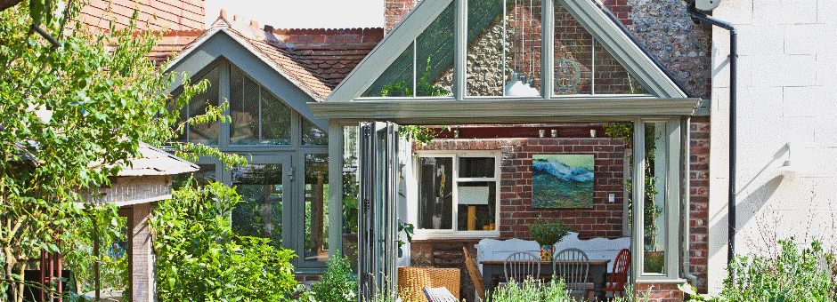 Aluminium conservatory with bi-fold doors and matching doors