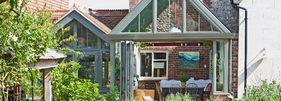 Aluminium conservatory with bi-fold doors and matching doors