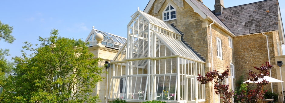 Double height classic Victorian greenhouse in aluminium - attached to the side of cottage for display