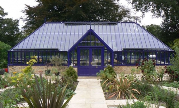 A bespoke freestanding greenhouse with hipped roof in purple