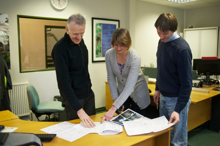 Design office team looking at greenhouse design plans