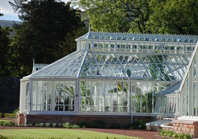 Large classic Victorian bespoke lean to greenhouse with a feature lobby and central display area